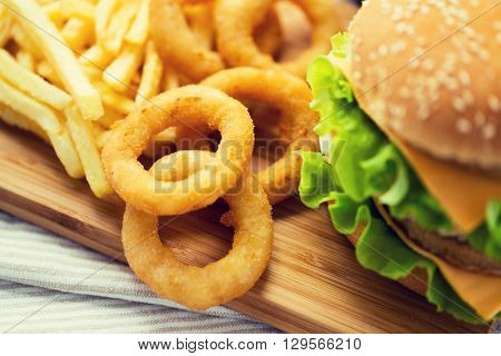 fast food, junk-food and unhealthy eating concept - close up of hamburger or cheeseburger, deep-fried squid rings and french fries on wooden table