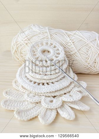 White vintage elements of Irish crochet. Cotton yarn for knitting crochet hook. Crochet doilies crochet pattern coasters on bamboo background