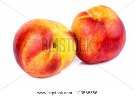 Two ripe nectarines on white background. Closeup.