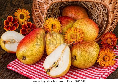 Red yellow ripe pears.  Basket with fresh pears on a rustic tablecloth.