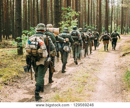 Unidentified Re-enactors Dressed As German Wehrmacht Soldier Walk In Summer Forest