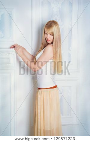 Fashion studio portrait of beautiful slim young woman with long blond hair, in white top and yellow skirt looking down