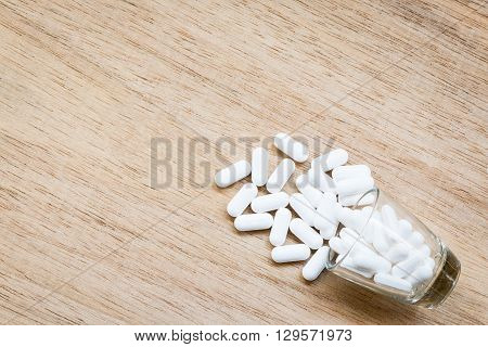 White pill in glass on wooden background