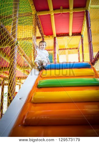 Little kid climbing on stairs in kindergarden playground