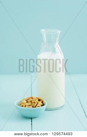 Fresh homemade walnut milk in a bottle with fresh walnuts