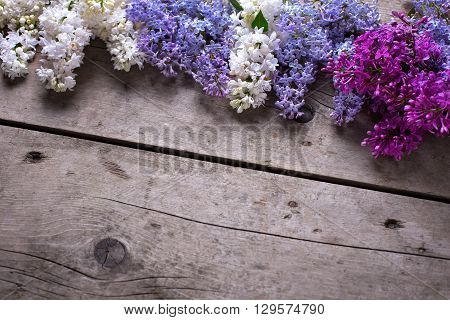 Background with fresh aromatic lilac flowers on vintage wooden planks. Selective focus. Place for text. Flat ley.