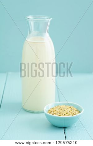 Fresh homemade oat milk in a bottle with oats