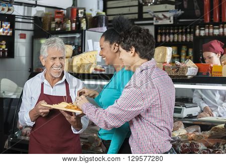Salesperson Offering Samples To Customers In Cheese Shop