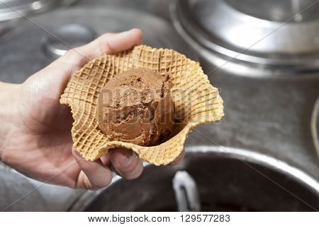 Hand Holding Chocolate Ice Cream In Waffle Bowl