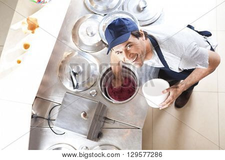 Waiter Filling Strawberry Ice Cream In Bowl At Counter poster