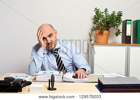 Manager Burnout. He holds his head with his hand
