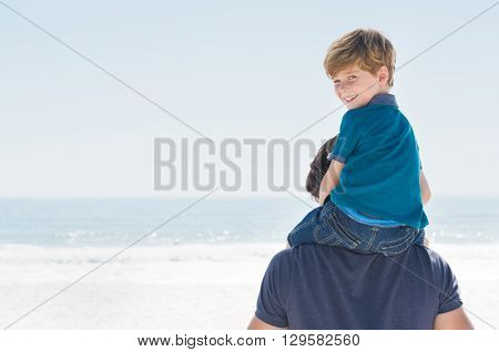 Young boy sitting on father shoulder. Happy son enjoying shoulder ride at beach, copy space. Son looking at camera and smiling at beach.