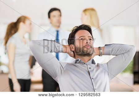 Portrait of a young businessman relaxing with hands behind head in office. Business man thinking of a new idea in office. Happy smiling man day dreaming while colleagues working in background.