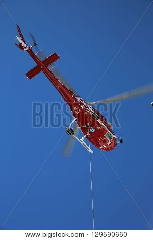 Saas-Fee, Switzerland - September 01, 2014: A Helicopter is transporting different things to the Britannia Hut (3030m above Sea) in the Swiss Alps
