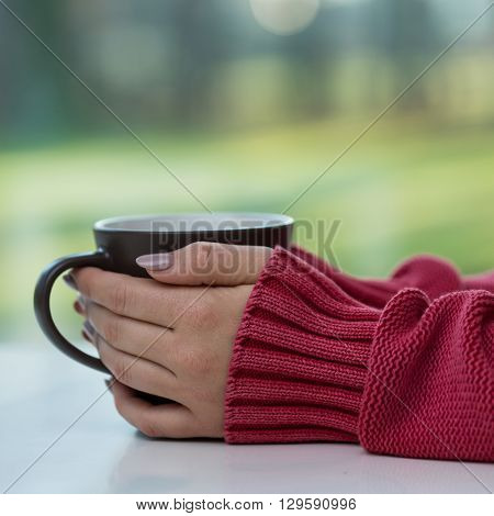 Close-up for young woman hands holding cup
