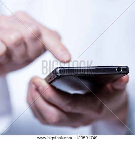 Close-up of hands of doctor using phone in hospital