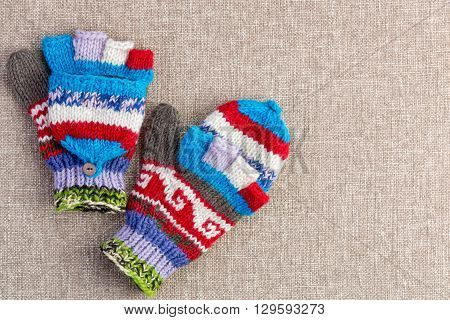 Colorful hand knitted convertible fingerless winter gloves with a fold back cap to cover the tips of the fingers as required on a beige textile background with copy space