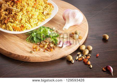 pilaf with garlic, raisins, olives, cardamom, parsley on a wooden cutting board