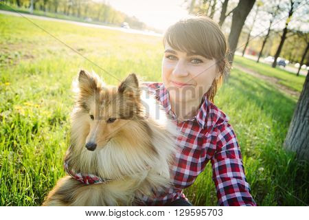 Young woman making selfie with her dog sheltie in the park on the green grass shetland sheepdog