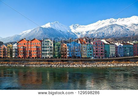 Innsbruck Austria - February 8 2010: The Mariahilf strasse colored houses on the Inn river with the snowy mountains in the background