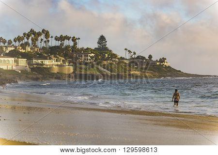 San Diego, USA - October 14, 2015: Man standing in ocean on the La Jolla coastline of Windansea Beach in San Diego, CA with houses on cliff.