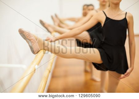 Closeup of a group of girls with their leg up in a barre during a ballet class at school