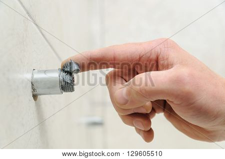 Plumber putting a paste sealant on the threads pipe. poster