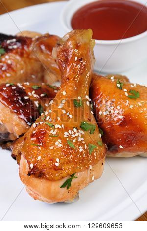 Fried chicken leg with sesame seeds in a plate and sauce