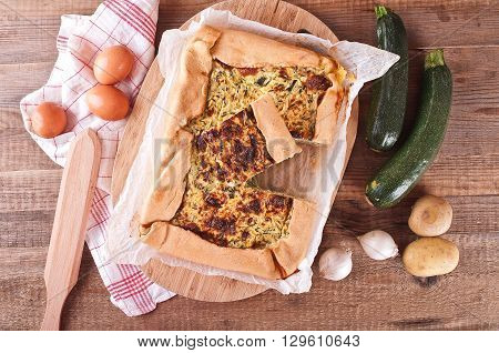 Image of zucchini savoury pie on wooden table.