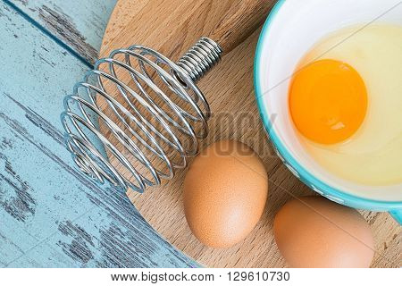 Chicken eggs and corolla of for whipping on a wooden board on a blue background.