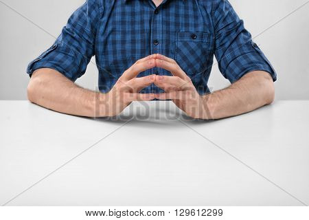 Cropped portrait of a man sitting with his clasped fingers. Readiness to talk. Symbols and gestures. Body language. Hand gesture. Readiness for work. Listen attentively. Straight posture.