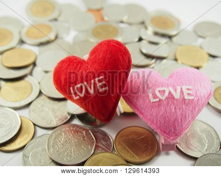 Little pillows with heart shape on pile of coins background (love collected coins saving money money for wedding in concept)
