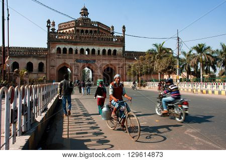 LUCKNOW, INDIA - DEC 19, 2012: Indian cyclist drives past the famouse gateway Rumi Darwaza at the sunny day on December 19,, 2012 in Lucknow India. Lucknow in Uttar Pradesh state has population of 4,588,455