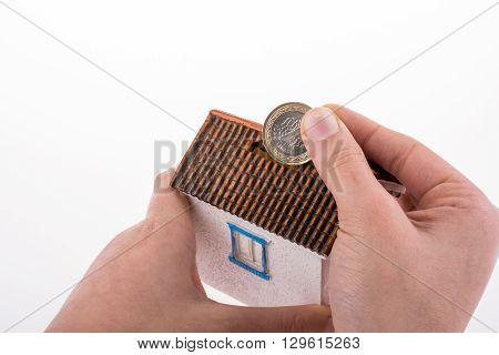 Hand dropping coin into the moneybox in the shape of a model house