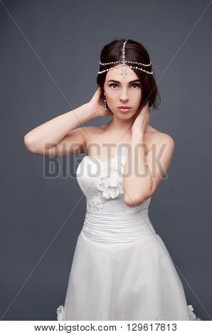 Brunette bride wearing tikka headpiece and white wedding dress. Bridal makeup and fashion.