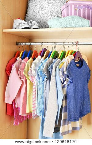 Kid's clothes on hangers in the wardrobe