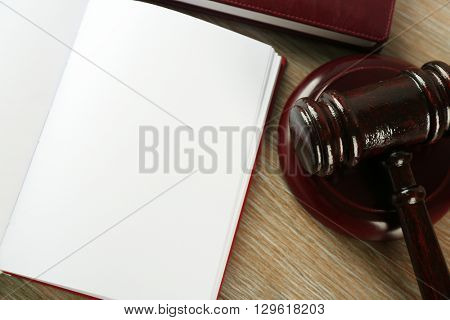 Wooden gavel and open book on wooden background
