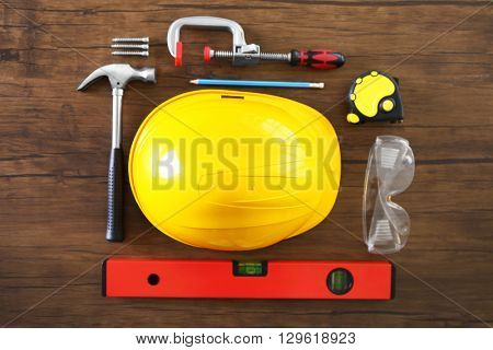 Helmet and construction tools on wooden table, top view