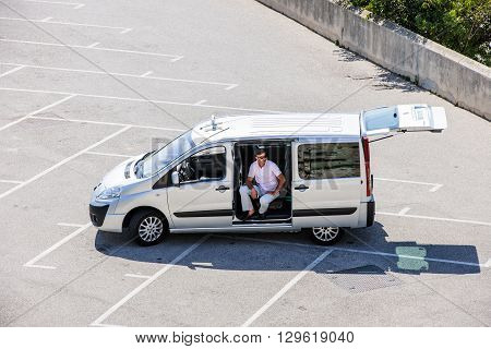 MARSEILLE FRANCE - JUL 18 2014: Elevated view of a man sitting int the empty light commercial vehicle taxi car (Peugeot Expert)