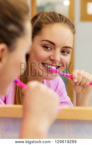 Woman brushing cleaning teeth. Girl with toothbrush in bathroom looking at mirror. Oral hygiene.