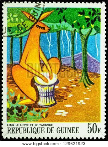MOSCOW RUSSIA - MAY 12 2016: A stamp printed in Guinea shows drumming hare in the forest series
