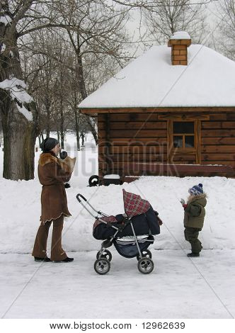 mother with children. snow. house.