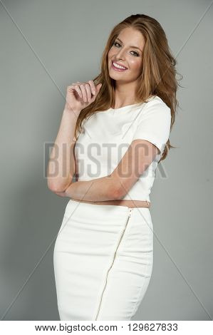 Beautiful young brunette female wearing a white tank top and white skirt, on a gray studio background.