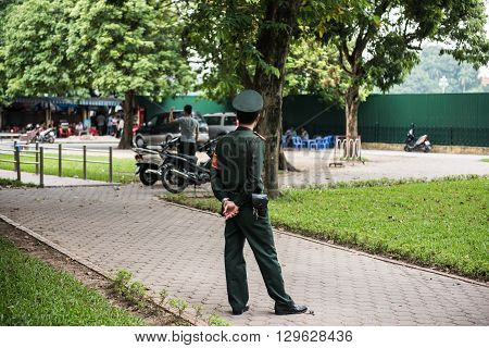 A hanoi city police with his gun standing on a street infront of the One Pillar Pagoda in Dien Bien province. Tourists and pedestrians along with a shop is seen.