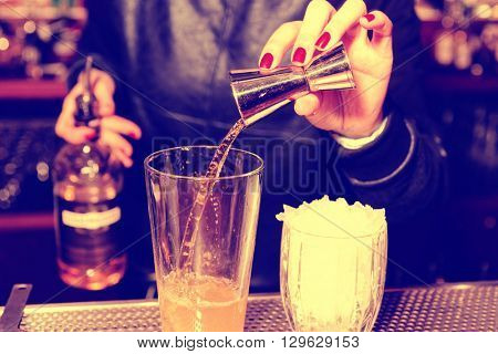 Female bartender is adding whisky to the mixing glass, toned