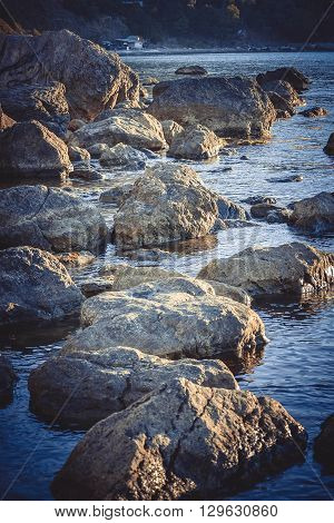 Large stones in the water near the shore filter