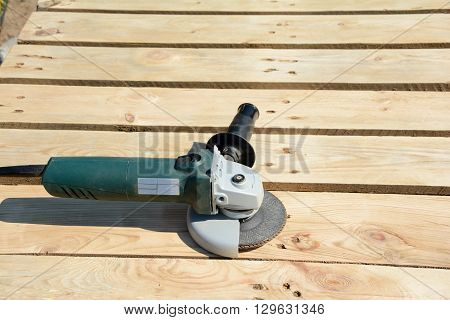Angle grinder with abrasive disc on planks after work.