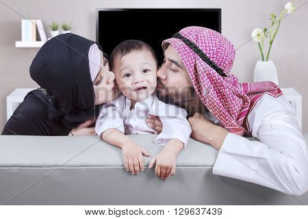 Two young Arabian parents kissing their son while sitting on the sofa in the living room