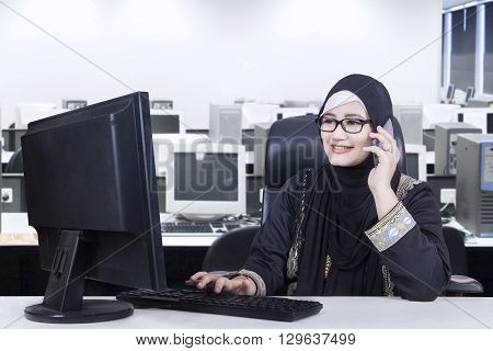 Pretty Arabian worker working in the office while wearing headscarf and talking on the mobile phone