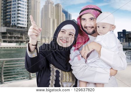 Happy middle eastern family wearing islamic clothes and looking at something in the city